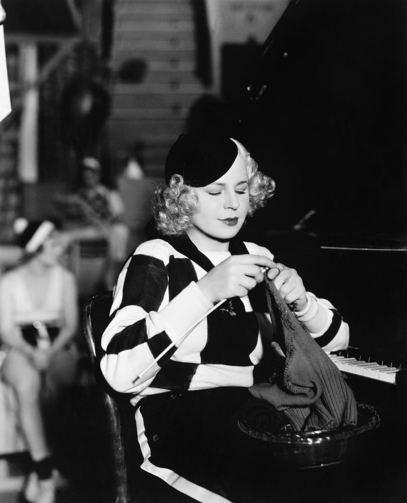 Young woman sitting and knitting at piano
