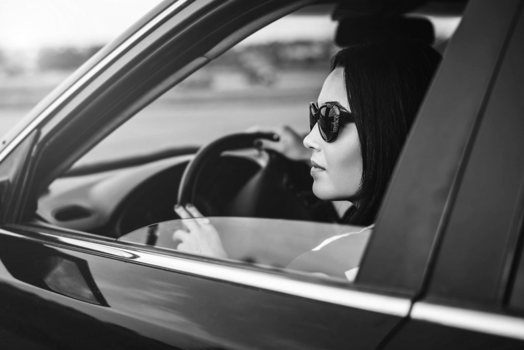 Brunette girl driving car on the road